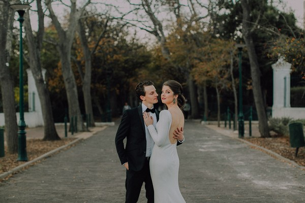 Bride and groom standing on tree-lined path