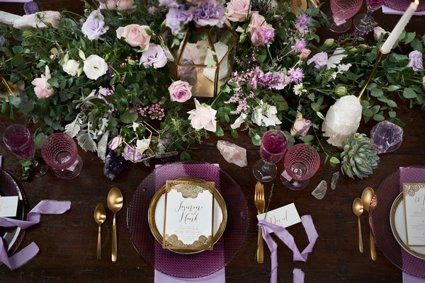Purple wedding place setting with large floral centrepiece
