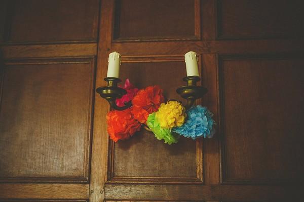 Colourful pom poms tie to candlesticks
