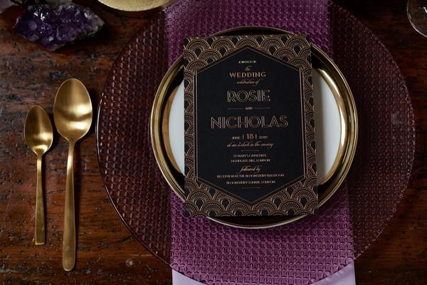 Black wedding stationery on purple plate