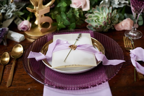 Wedding stationery with seal, ribbon and lavender on purple plate