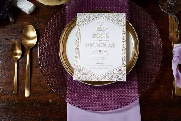 Art-Deco style wedding stationery on purple plate