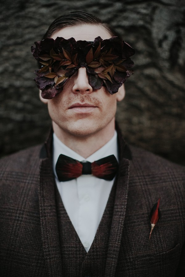 Groom with foliage mask over eyes