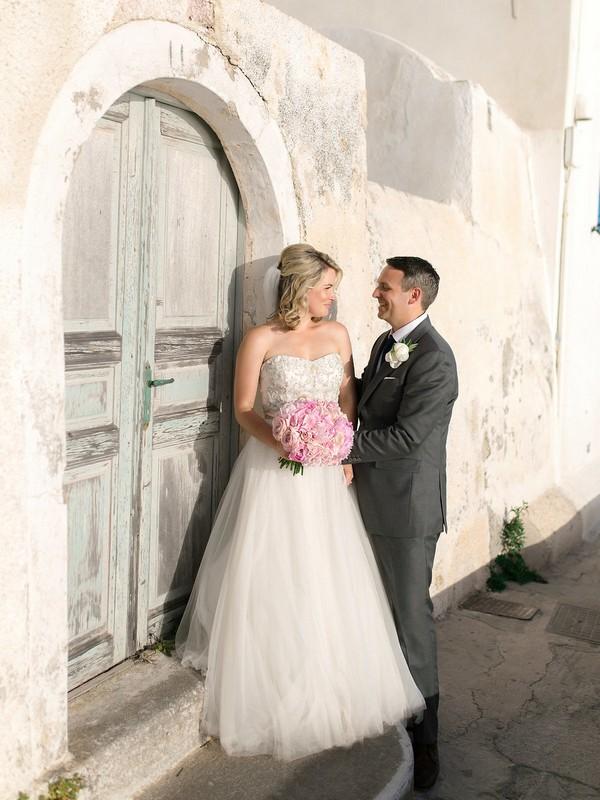 Bride and groom standing in front of old door in Santorini