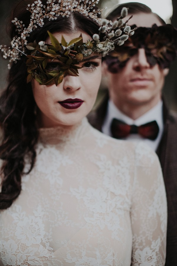 Bride and groom with foliage mask over eyes