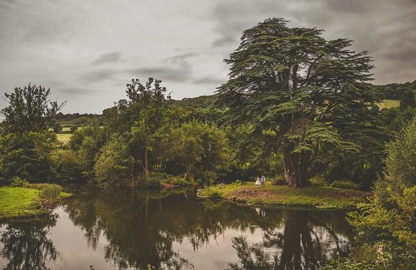 Bride and groom by lake at Colehayes Park