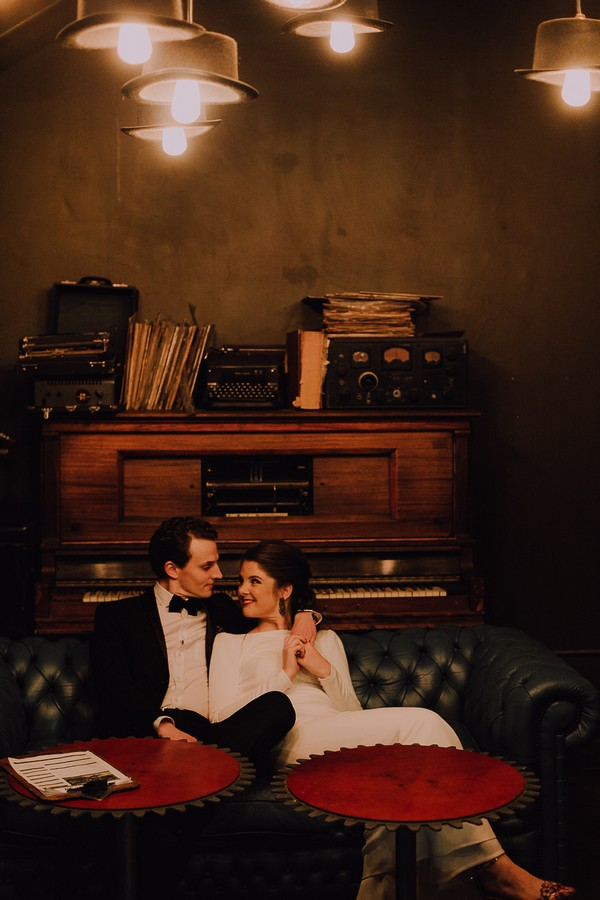 Bride and groom sitting on couch in Centre for the Book
