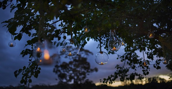 Glass baubles with tea lights hanging from tree