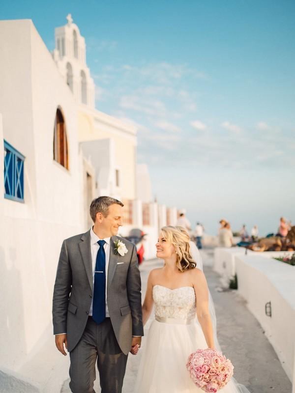 Bride and groom walking down street in Santorini