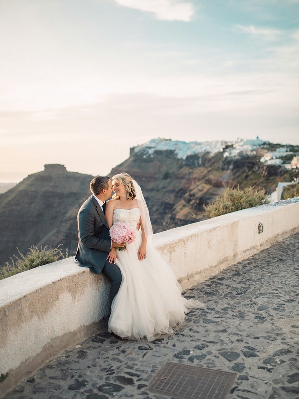 Bride and groom sitting on wall in Santorini