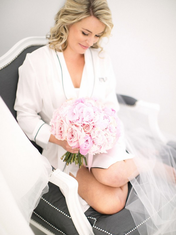 Bride sitting with bouquet before getting dressed