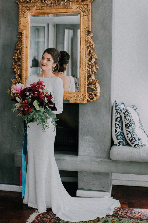 Bride holding bouquet in front of mirror