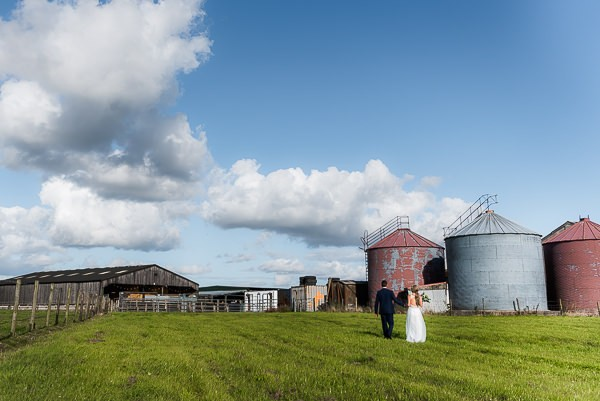 Bride and groom walking across farm