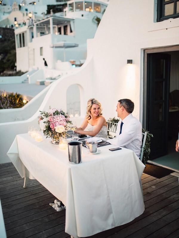 Couple having dinner after elopement in Santorini