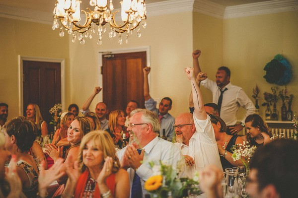 Wedding guests holding arms up