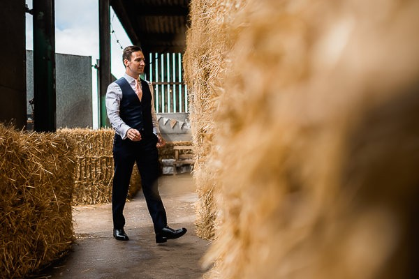 Groomsman walking into cow shed