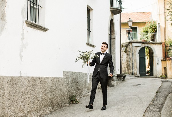 Groom carrying bride's bouquet down street in Lake Como