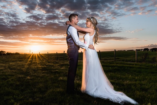 Bride and groom in field as sun sets