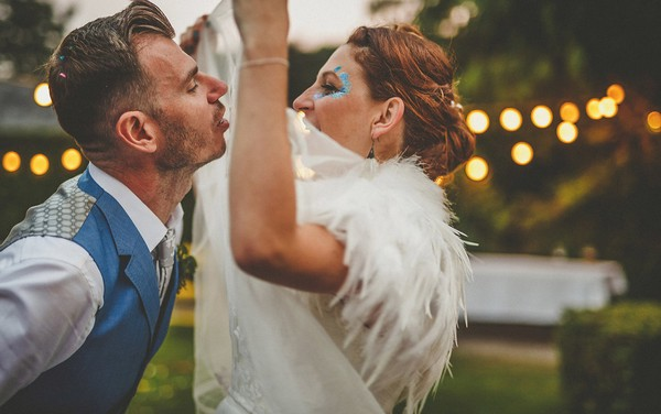 Groom about to kiss bride wearing feather shrug