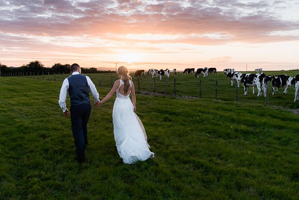 Bride and groom walking across field at farm