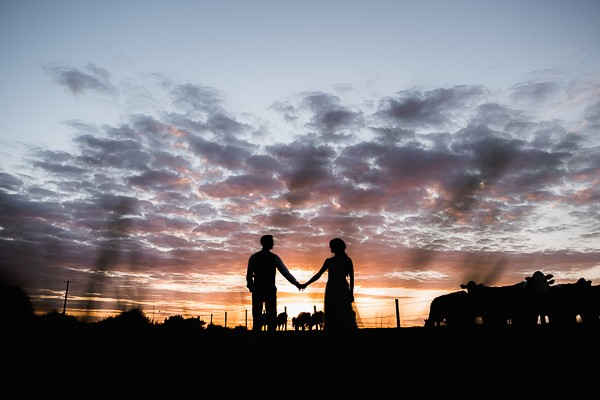 Silhouette of bride and groom against dusky sky