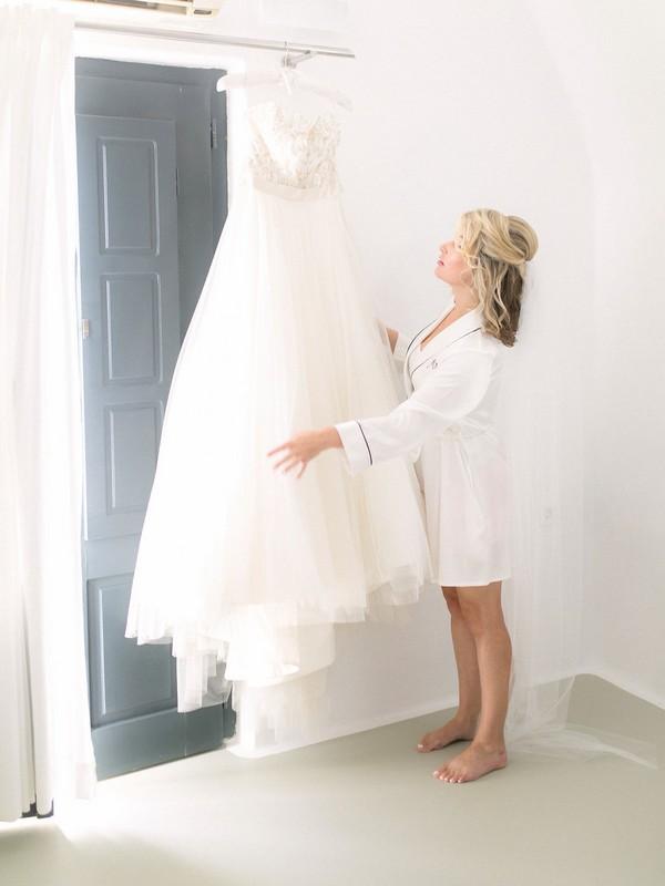 Bride taking wedding dress down off door