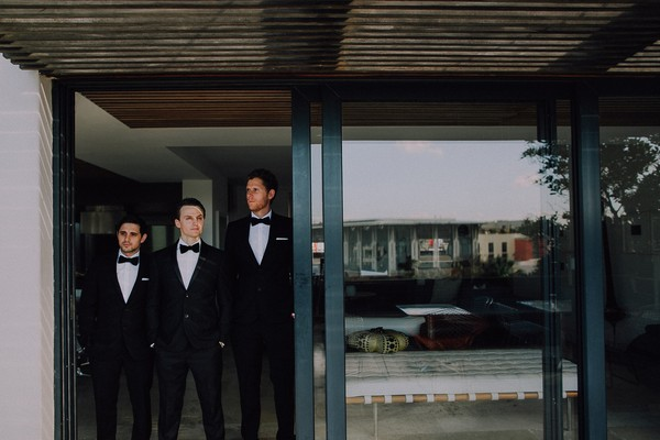 Groomsmen standing by sliding glass door