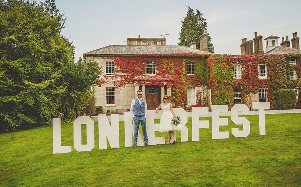 Bride and groom standing in front of Lonkerfest sign at Colehayes Park wedding