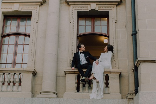 Bride and groom sitting on balcony of Centre for the Book