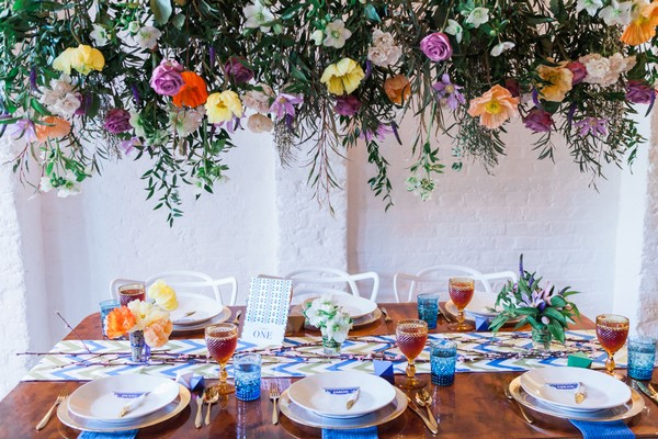 Urban tribal wedding table styling under hanging floral display