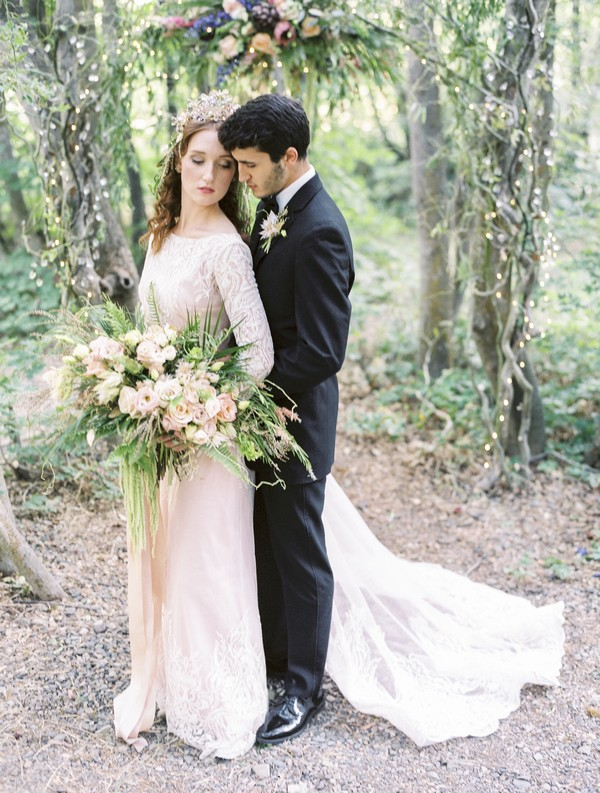 Groom standing behind bride in woods