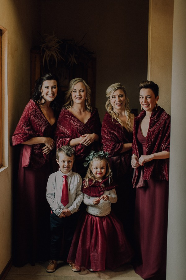 Bridesmaids in burgundy dresses with flower girl and pageboy