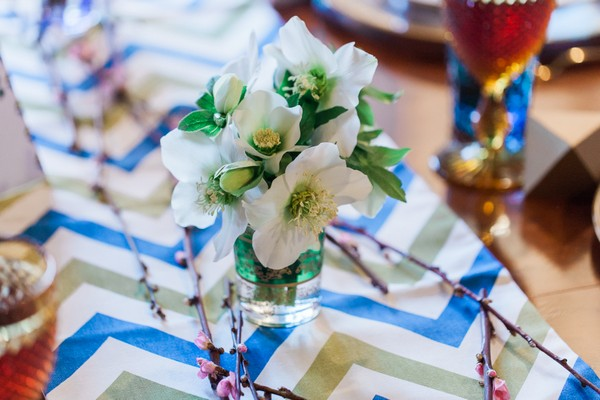 Green and white wedding table flowers on chevron runner