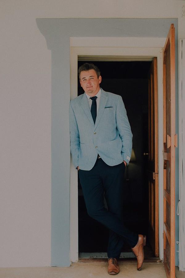 Groom leaning in doorway