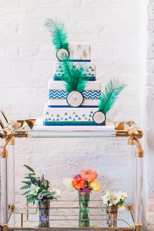 Wedding cake with geometric, green feather and dreamcatcher details on trolley