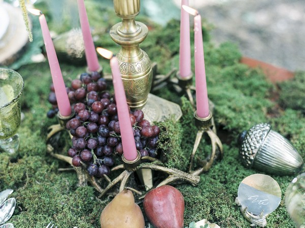 Candles on moss covered wedding table