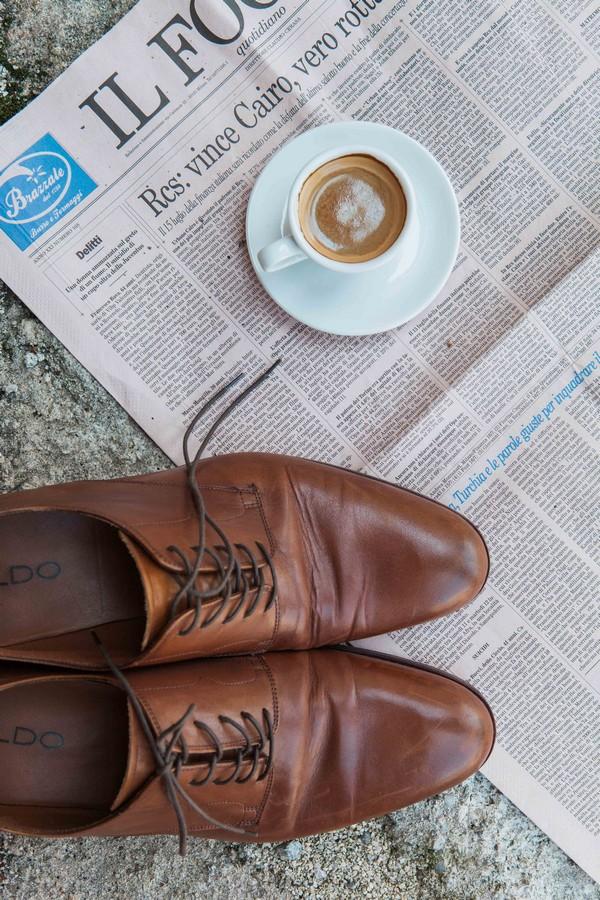 Brown groom shoes on newspaper