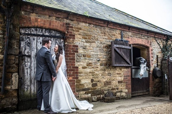 Bride and groom outside stable with horse looking at them - Picture by Carrie Lavers Photography