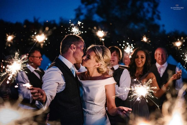 Bride and groom kissing as they and their guests hold sparklers - Picture by Kazooieloki