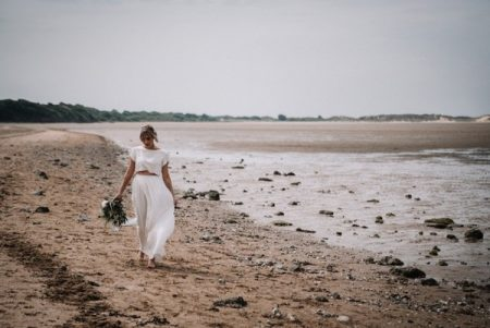 Bride walking on beach carrying bouquet - Picture by Oobaloos Photography