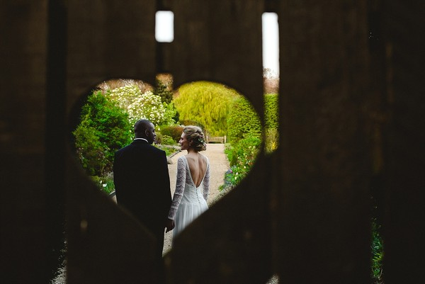 Bride and groom seen through heart shaped hole in gate - Picture by Anesta Broad Photography