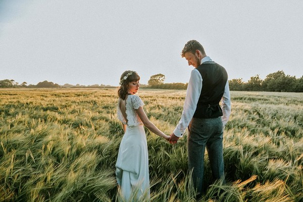 Bride and groom holding hands in long grass - Picture by Ruby-Roux Photography