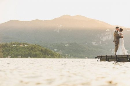 Bride and groom kissing on jetty with mountain background - Picture by Sam & Louise