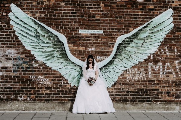 Bride standing against wall with huge wings on it - Picture by Ian MacMichael Photography