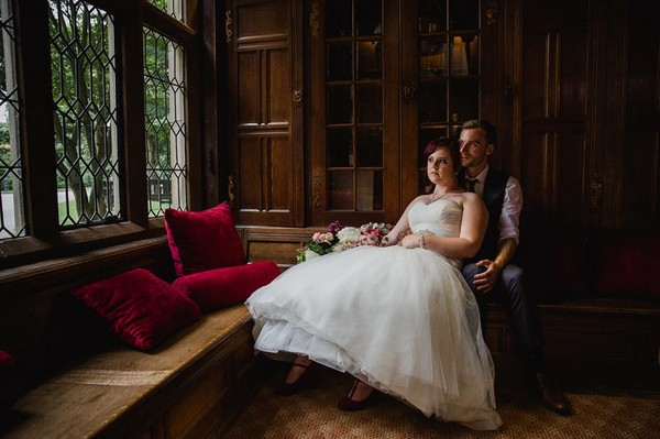 Bride and groom sitting looking out of window of venue - Picture by Helen King Photography