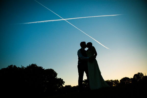 Bride and groom kissing with a vapour trail cross above their heads - Picture by Ketch 22 Photography