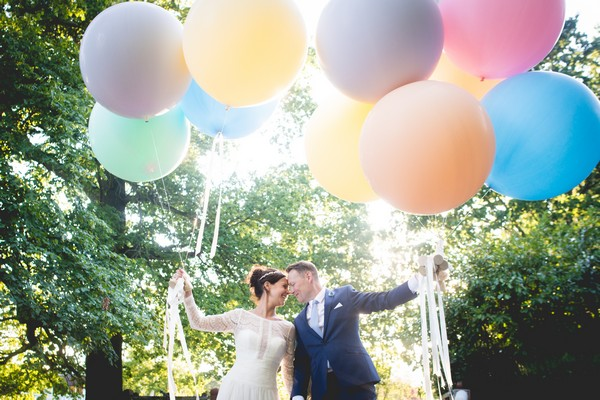 Bride and groom touching heads holding colourful balloons - Picture by Nicola Norton Photography