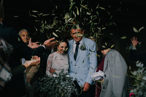Bride and groom being showered in leaves