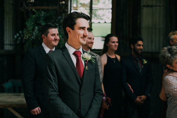 Groom watching bride walk into wedding ceremony