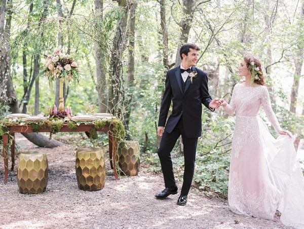 Bride and groom by wedding table in woods